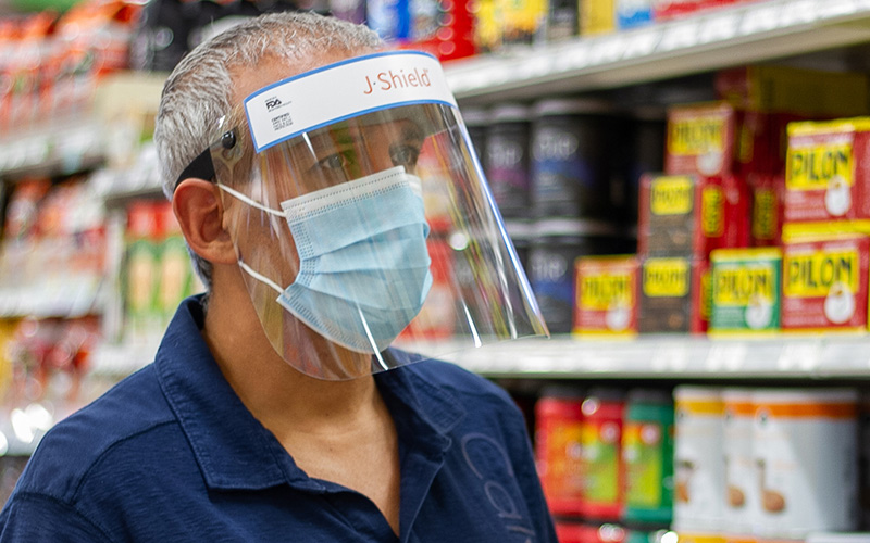 Shopper looking at grocery store shelf wearing a J-Shield Face Shield