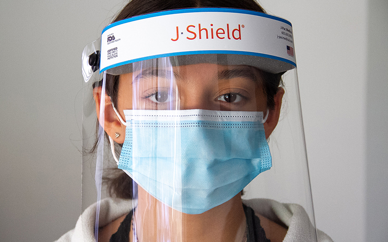 A woman facing forward while wearing a J-Pac Face Shield X and a surgical mask