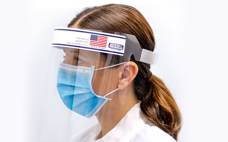 A nurse wearing a Covid face shield with an adjustable strap. The shield's label shows the Made in America label.