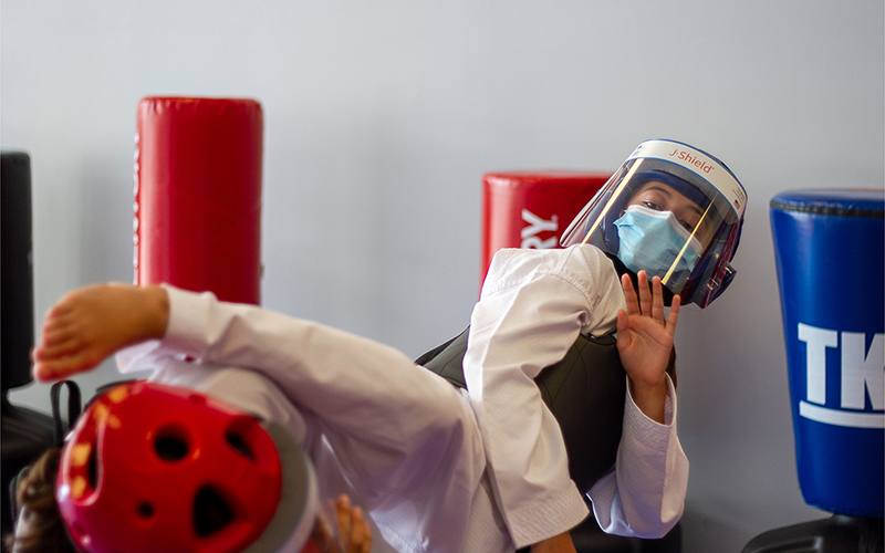 A girl training in martial arts wearing a COVID face shield while sparing