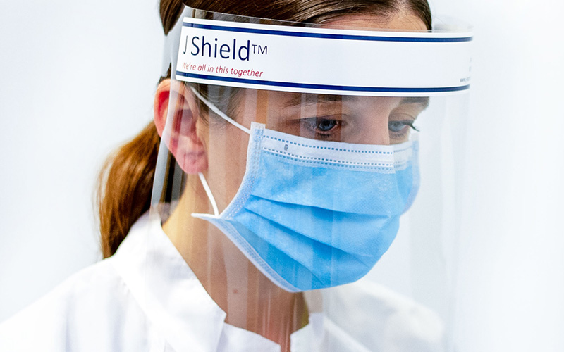 A hospital nurse wearing a plastic medical face shield and a surgical mask while looking down at a patient.