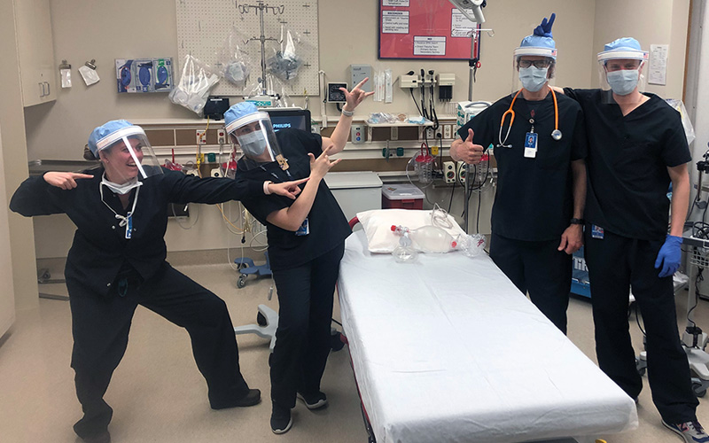 A team of doctors and nurses wearing face shields in the operating room while having fun posing for the picture.